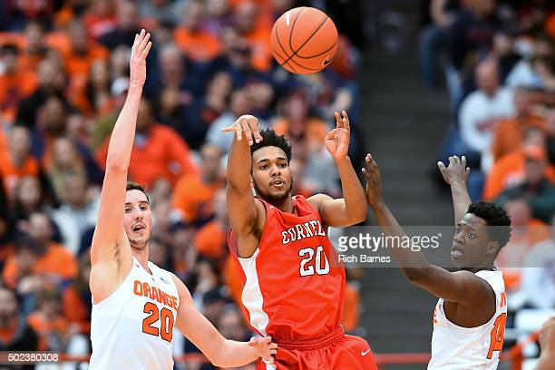 Wil Bathurst of the Cornell Big Red passes the ball between Tyler Lydon and Kaleb Joseph of the Syracuse Orange during the first half at the Carrier...