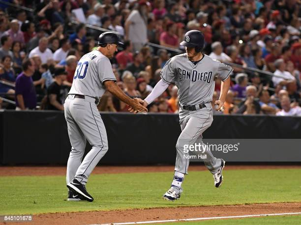 Wil Myers of the San Diego Padres celebrates with third base coach Glenn Hoffman after hitting a two run home run off of Zack Godley of the Arizona...