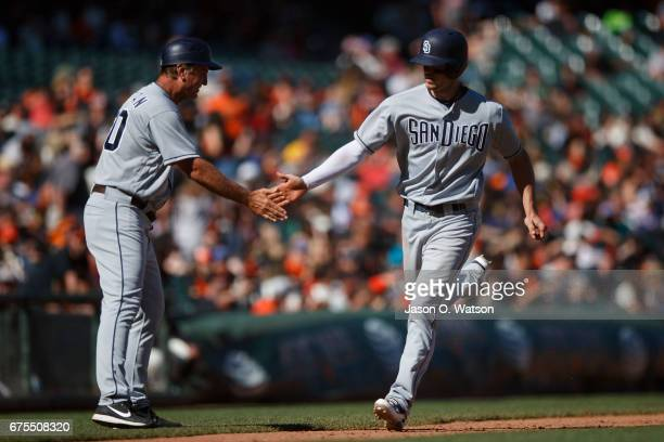 Wil Myers of the San Diego Padres is congratulated by third base coach Glenn Hoffman after hitting a three run home run against the San Francisco...