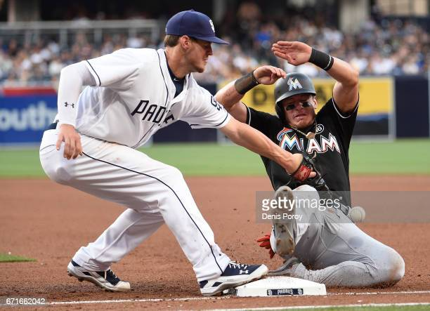 Wil Myers of the San Diego Padres loses the ball as Derek Dietrich of the Miami Marlins gets back to first base during the fifth inning of a baseball...