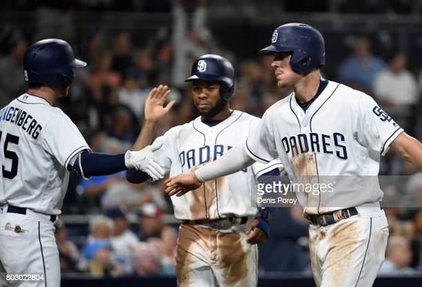 Wil Myers of the San Diego Padres right and Manuel Margot are congratulated by Cory Spangenberg after scoring during the fourth inning of a baseball...
