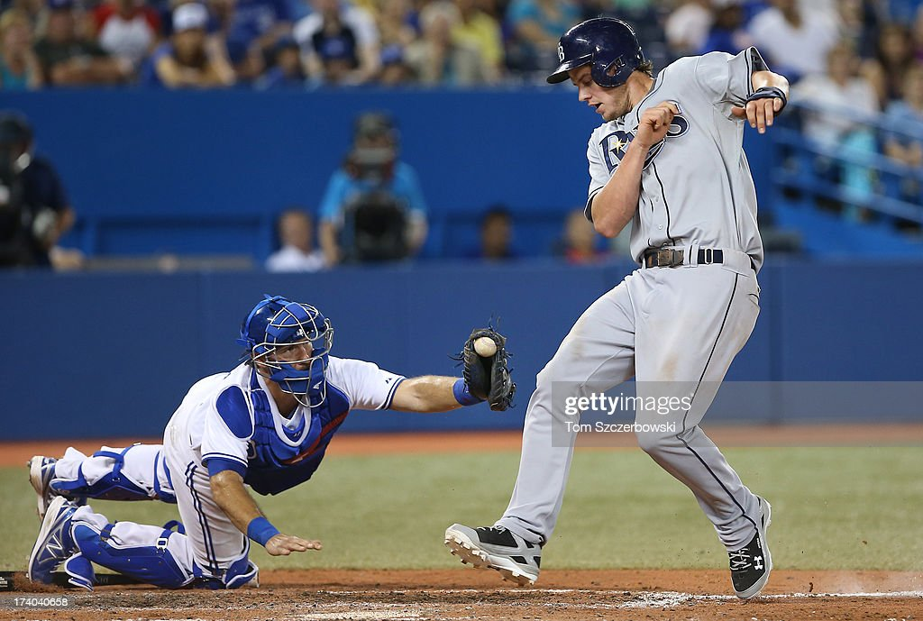 <a gi-track='captionPersonalityLinkClicked' href=/galleries/search?phrase=Wil+Myers&family=editorial&specificpeople=7562808 ng-click='$event.stopPropagation()'>Wil Myers</a> #9 of the Tampa Bay Rays evades the tag of <a gi-track='captionPersonalityLinkClicked' href=/galleries/search?phrase=J.P.+Arencibia&family=editorial&specificpeople=4959430 ng-click='$event.stopPropagation()'>J.P. Arencibia</a> #9 of the Toronto Blue Jays to score a run in the ninth inning during MLB game action on July 19, 2013 at Rogers Centre in Toronto, Ontario, Canada.