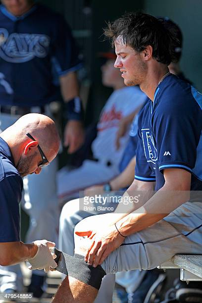 Wil Myers of the Tampa Bay Rays holds his left knee as he is tended to by medical staff after stealing second base during the fourth inning of a...