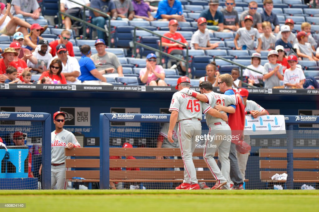 Wil Nieves #21 of the Philadelphia Phillies is helped off the field following an injury during the ninth inning at Turner Field on June 18, 2014 in Atlanta, Georgia.