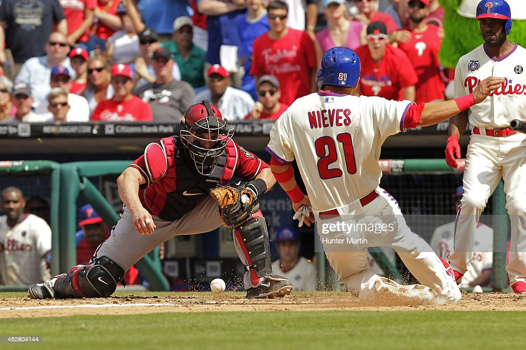 <a gi-track='captionPersonalityLinkClicked' href=/galleries/search?phrase=Wil+Nieves&family=editorial&specificpeople=835752 ng-click='$event.stopPropagation()'>Wil Nieves</a> #21 of the Philadelphia Phillies slides safely into home as catcher <a gi-track='captionPersonalityLinkClicked' href=/galleries/search?phrase=Miguel+Montero&family=editorial&specificpeople=836495 ng-click='$event.stopPropagation()'>Miguel Montero</a> #26 of the Arizona Diamondbacks drops the ball in the seventh inning during a game at Citizens Bank Park on July 27, 2014 in Philadelphia, Pennsylvania. The Phillies won 4-2.