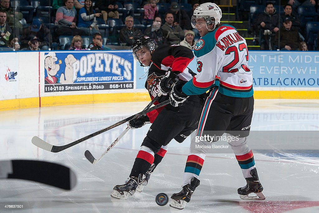 Wil Tomchuk #5 of the Prince George Cougars makes a back pass as Justin Kirkland #23 of the Kelowna Rockets checks him on February 25, 2014 at Prospera Place in Kelowna, British Columbia, Canada.