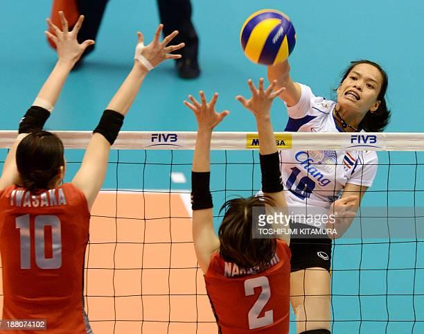 Wilavan Apinyapong of Thailand spikes the ball past Japan's Nana Iwasaka and Hitomi Nakamichi during their FIVB volleyball women's Grand Champions...