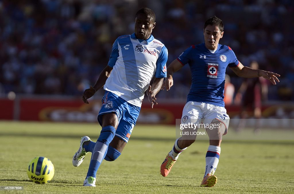 Wilberto Cosme of Puebla vies for the ball with Fausto Pinto of Cruz Azul during their Mexican Clausura tournament football match at the Cuauthemoc...