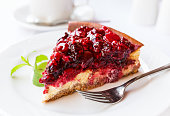 Wild berries cake with green mint on plate with fork. Selective focus