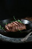Pan fried wild boar fillet with seasoning and rosemary herb garnish in a iron skillet shot against a rustic background and wood burner stove. Copy space.