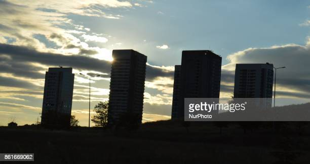 A wild field is seen as the sun beams beyond tall residential buildings under construction in Ankara Turkey on October 15 2017 Expected growth...