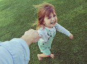 Silly little girl holding a parents hand barefoot in the grass, laughing