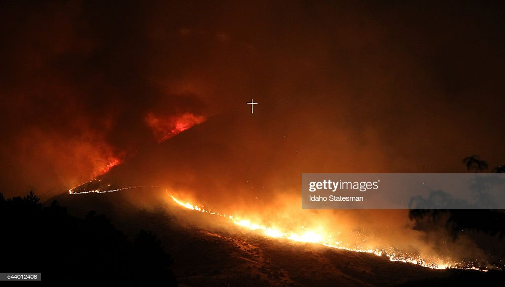 A wildfire fire burns near the Table Rock cross in Boise, Idaho, in the early morning hours of Thursday, June 30, 2016.