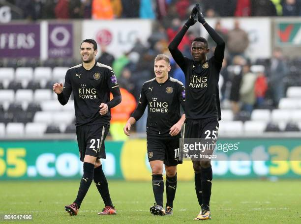 Wilfred Ndidi Marc Albrighton and Vicente Iborra of Leicester City celebrate after the final whistle of the Premier League match between Swansea City...