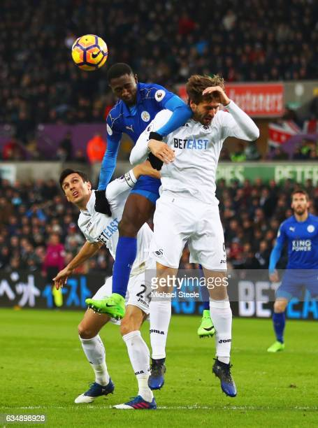 Wilfred Ndidi of Leicester City jumps between Fernando Llorente and Jack Cork of Swansea City during the Premier League match between Swansea City...