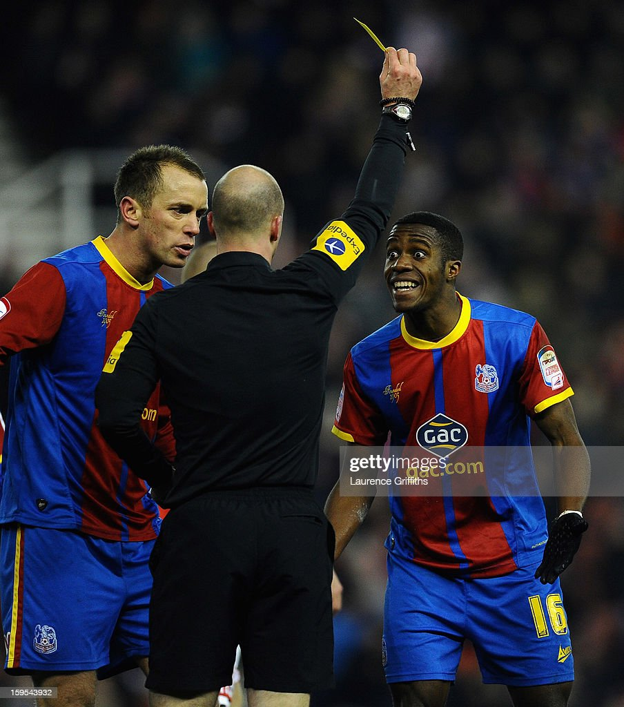 Wilfred Zaha of Crystal Palace is booked for diving by Referee Anthony Taylor during the FA Cup with Budweiser Third Round replay match between Stoke City and Crystal Palace at Britannia Stadium on January 15, 2013 in Stoke on Trent, England.