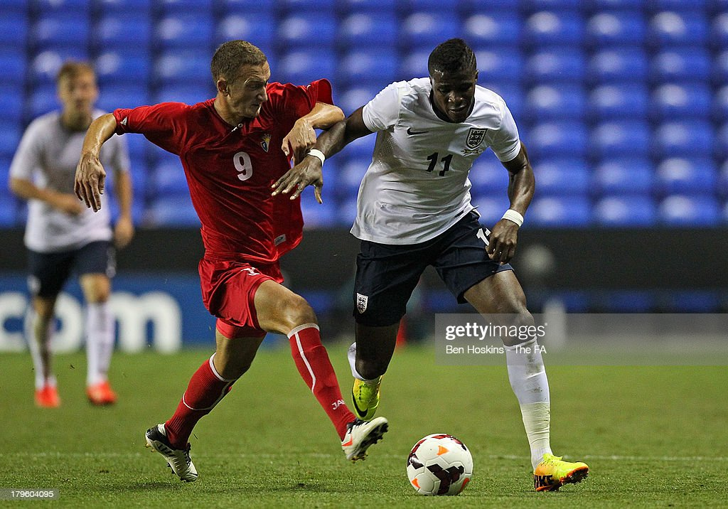Wilfred Zaha of England (R) and Gheorghe Anton of Moldova battle for the ball during the 2015 UEFA European U21 Championships Qualifier match between England U21 and Moldova U21 at Madejski Stadium on September 5, 2013 in Reading, England.