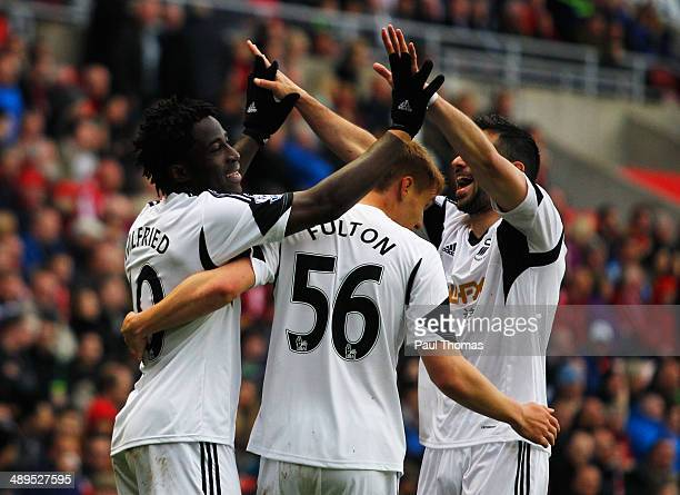 Wilfried Bony of Swansea City celebrates with Jay Fulton and Jordi Amat as he scores their third goal during the Barclays Premier League match...