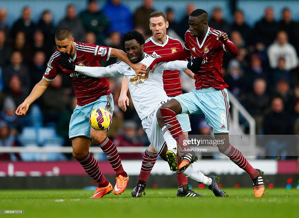 Wilfried Bony of Swansea City is closed down by Winston Reid (L) Kevin Nolan and Cheikhou Kouyate (R) of West Ham during the Barclays Premier League match between West Ham United and Swansea City at Boleyn Ground on December 7, 2014 in London, England.