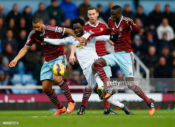 Wilfried Bony of Swansea City is closed down by Winston Reid Kevin Nolan and Cheikhou Kouyate of West Ham during the Barclays Premier League match...