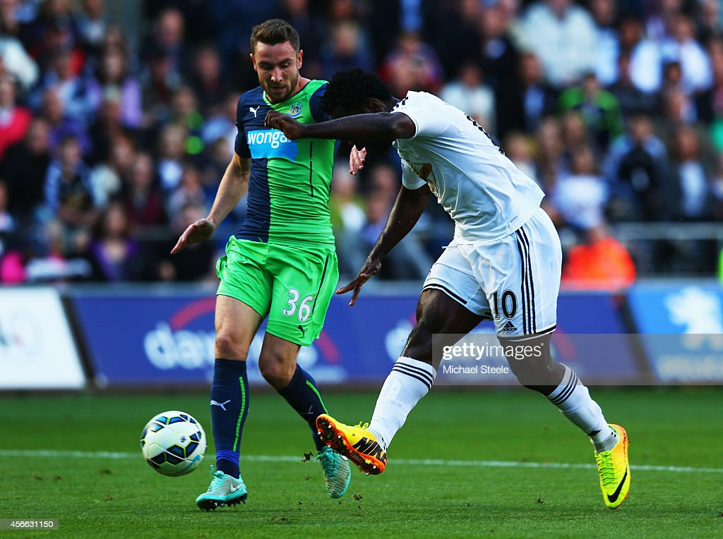 Wilfried Bony of Swansea City shoots past Paul Dummett of Newcastle United to score their first goal during the Barclays Premier League match between Swansea City and Newcastle United at Liberty Stadium on October 4, 2014 in Swansea, Wales.