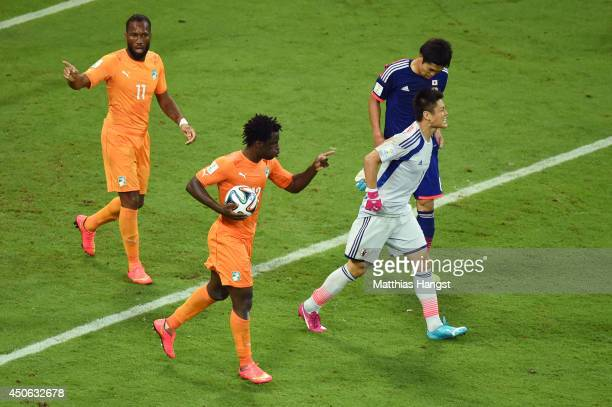 Wilfried Bony of the Ivory Coast celebrates scoring his team's first goal with Didier Drogba as goalkeeper Eiji Kawashima of Japan reacts during the...