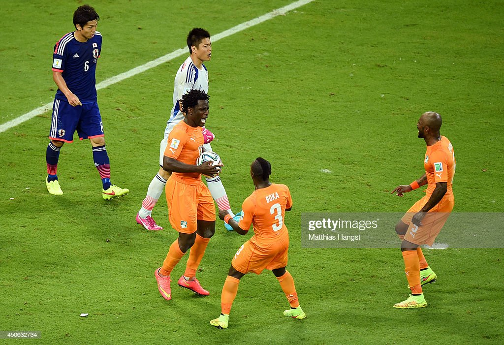 Wilfried Bony of the Ivory Coast celebrates scoring his team's first goal with Arthur Boka and Didier Zokora as goalkeeper Eiji Kawashima of Japan...