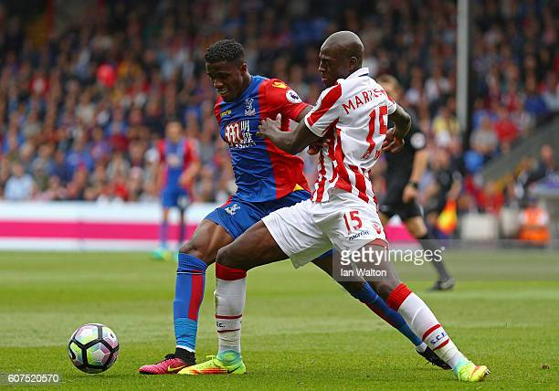 Wilfried Zaha of Crystal Palace and Bruno Martins Indi of Stoke City battle for possession during the Premier League match between Crystal Palace and...