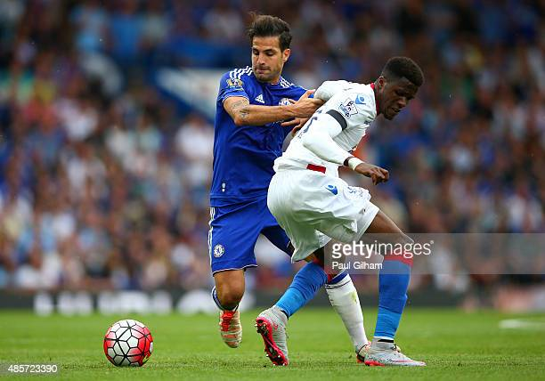 Wilfried Zaha of Crystal Palace and Cesc Fabregas of Chelsea compete for the ball during the Barclays Premier League match between Chelsea and...