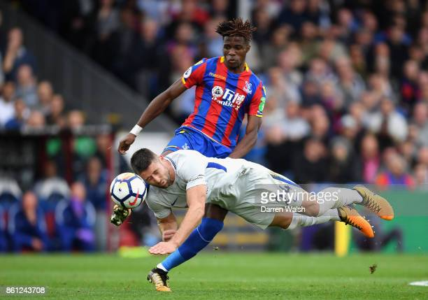 Wilfried Zaha of Crystal Palace and Gary Cahill of Chelsea battle for possession during the Premier League match between Crystal Palace and Chelsea...