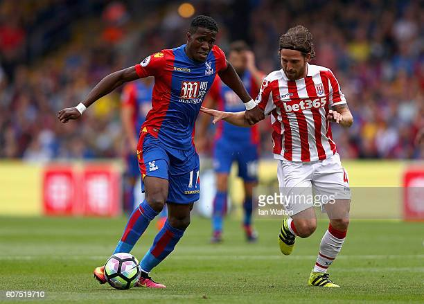 Wilfried Zaha of Crystal Palace and Joe Allen of Stoke City battle for possession during the Premier League match between Crystal Palace and Stoke...