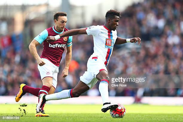 Wilfried Zaha of Crystal Palace and Mark Noble of West Ham United compete for the ball during the Barclays Premier League match between West Ham...