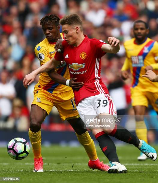 Wilfried Zaha of Crystal Palace and Scott McTominay of Manchester United battle for possession during the Premier League match between Manchester...