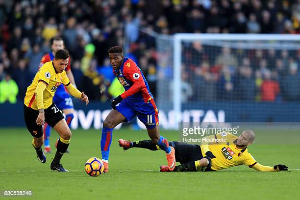 Wilfried Zaha of Crystal Palace battles for the ball with Adlene Guedioura of Watford and Jose Holebas of Watford during the Premier League match...