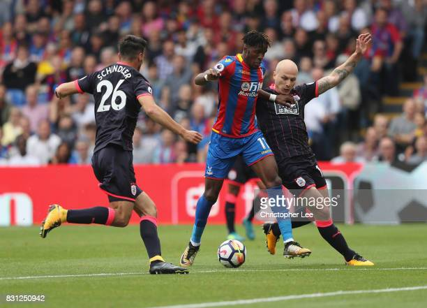 Wilfried Zaha of Crystal Palace battles with Aaron Mooy of Huddersfield Town and Christopher Schindler of Huddersfield Town during the Premier League...