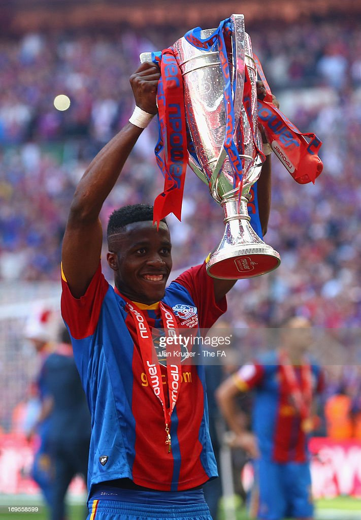 <a gi-track='captionPersonalityLinkClicked' href=/galleries/search?phrase=Wilfried+Zaha&family=editorial&specificpeople=7132531 ng-click='$event.stopPropagation()'>Wilfried Zaha</a> of Crystal Palace celebrates with the trophy following his team's victory in extra-time during the npower Championship Play-off Final match between Watford and Crystal Palace at Wembley Stadium on May 27, 2013 in London, England.