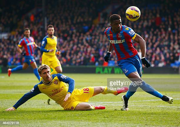 Wilfried Zaha of Crystal Palace evades Nacho Monreal of Arsenal during the Barclays Premier League match between Crystal Palace and Arsenal at...