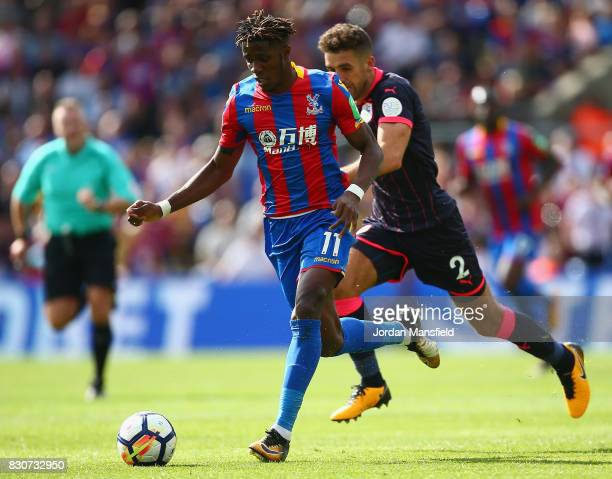 Wilfried Zaha of Crystal Palace gets away from Tommy Smith of Huddersfield Town during the Premier League match between Crystal Palace and...