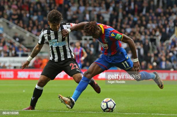 Wilfried Zaha of Crystal Palace holds off Deandre Yedlin of Newcastle United during the Premier League match between Newcastle United and Crystal...