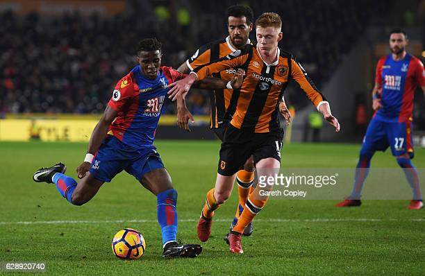 Wilfried Zaha of Crystal Palace holds off Sam Clucas of Hull City as he scores their second goal during the Premier League match between Hull City...