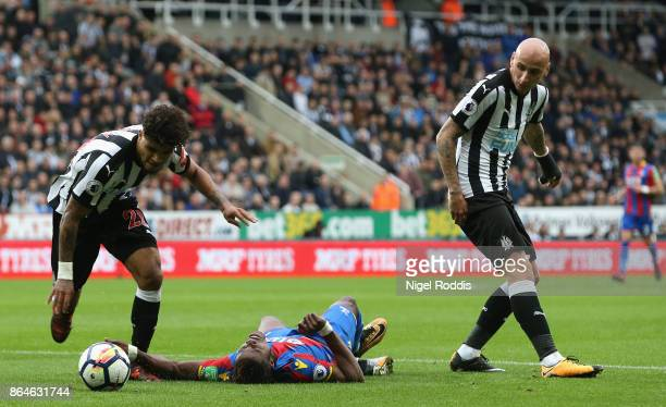 Wilfried Zaha of Crystal Palace is foiled by Deandre Yedlin and Jonjo Shelvey of Newcastle United during the Premier League match between Newcastle...
