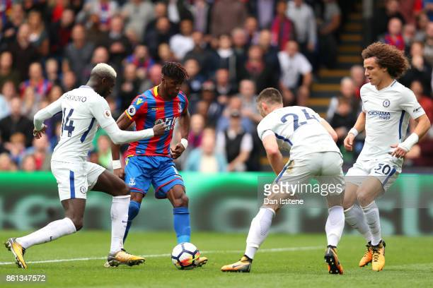 Wilfried Zaha of Crystal Palace runs with the ball under pressure from Tiemoue Bakayoko Gary Cahill and David Luiz of Chelsea during the Premier...