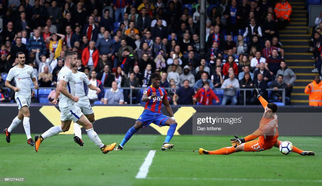 Wilfried Zaha of Crystal Palace scores his sides second goal past Thibaut Courtois of Chelsea during the Premier League match between Crystal Palace and Chelsea at Selhurst Park on October 14, 2017 in London, England.