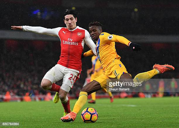 Wilfried Zaha of Crystal Palace shoots under pressure from Hector Bellerin of Arsenal during the Premier League match between Arsenal and Crystal...
