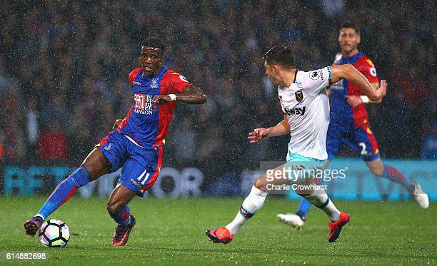 Wilfried Zaha of Crystal Palace takes on Aaron Cresswell of West Ham United during the Premier League match between Crystal Palace and West Ham...
