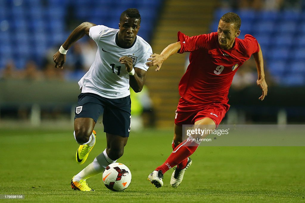 Wilfried Zaha of England holds off Gheorghe Anton of Moldova during the 2015 UEFA European U21 Championships Qualifier between England U21 and Moldova U21 at the Madejski Stadium on September 5, 2013 in Reading, England.