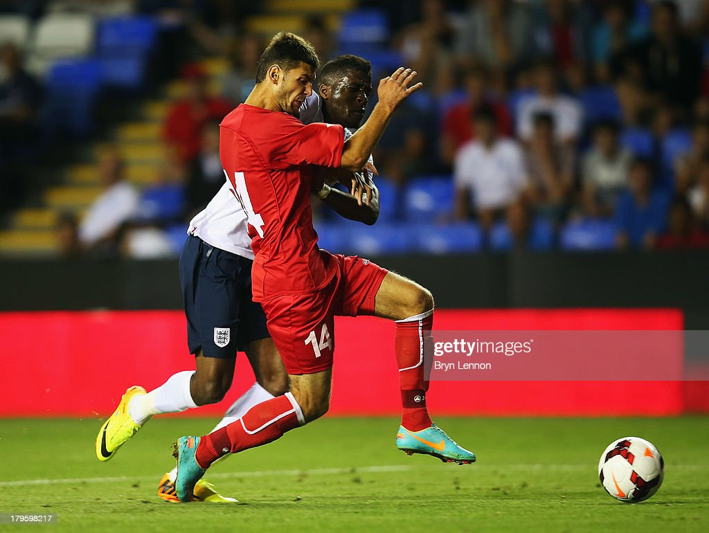 Wilfried Zaha of England holds off Iurie Mirza of Moldova during the 2015 UEFA European U21 Championships Qualifier between England U21 and Moldova U21 at the Madejski Stadium on September 5, 2013 in Reading, England.