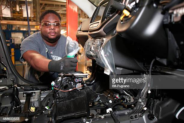 Wilhem Sandeau of Detroit Michigan installs a shifter in a 2014 Jeep Cherokee at the Chrysler Toledo North Assembly Plant Jeep May 7 2014 in Toledo...