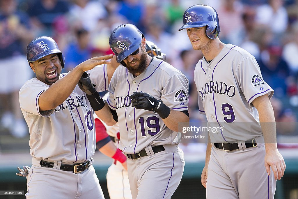 Wilin Rosario and Vinny Castilla celebrate with Charlie Blackmon of the Colorado Rockies after all scored on a home run by Blackmon during the...