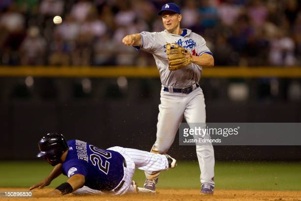 Wilin Rosario of the Colorado Rockies breaks up a double play attempt at second base by Mark Ellis of the Los Angeles Dodgers during the seventh...